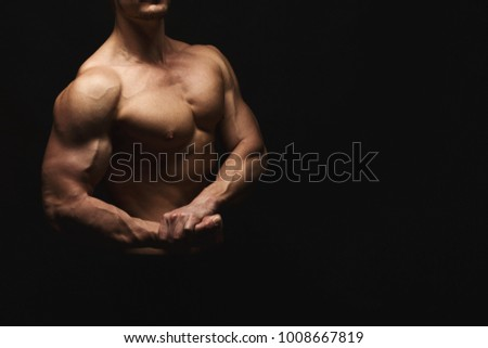 Strong athletic man. Handsome male fitness model showing naked torso, muscular body. Strong hands, chest and shoulder muscles and biceps. Studio shot on black background, low key. Bodybuilding concept