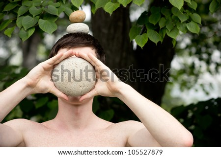 Strong athletic man holding a pile of stones in balance on his head, covering her face with a stone. Get the balance concept. - stock photo