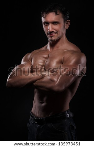 Strong athletic man isolated on black background - stock photo
