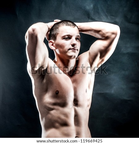 strong athletic man on a black background - stock photo