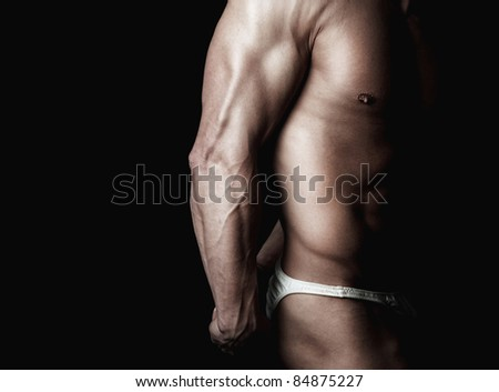 strong athletic man on black background demonstrates his body