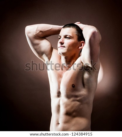 strong athletic man on brown background - stock photo