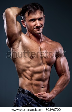 strong athletic man on dark background - stock photo