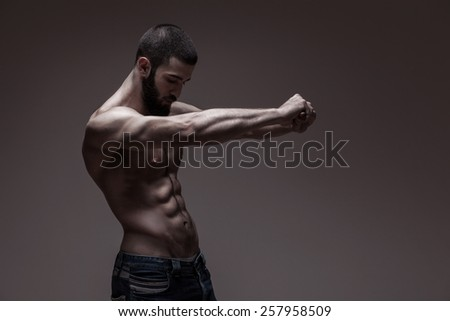 strong athletic man on dark grey gradient background - stock photo