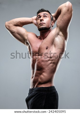 Strong athletic man posing over gray background