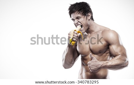 Strong Athletic Man  showing muscular body and eating a banana over white background - stock photo