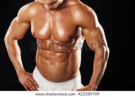 Strong Athletic Man showing muscular body over black background.Muscular man on black background