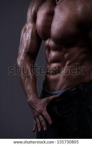 Strong athletic man torso isolated on black background - stock photo