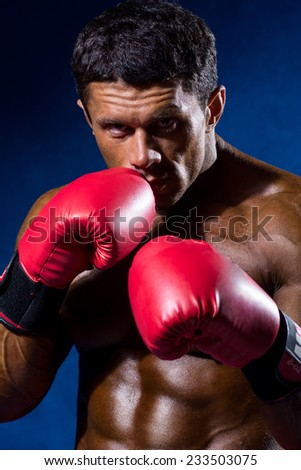 Strong athletic man with boxing gloves on a blue background. - stock photo