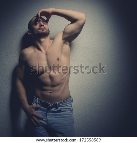 Strong athletic man with perfect body posing in studio on black background, toned
