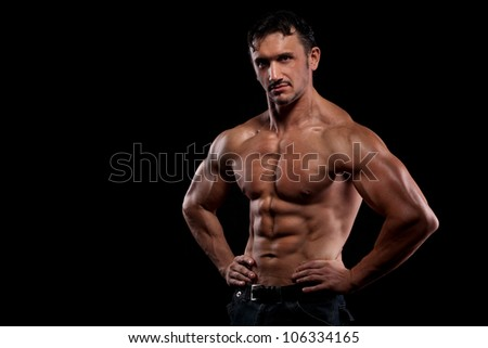 strong athletic mans back on dark background - stock photo