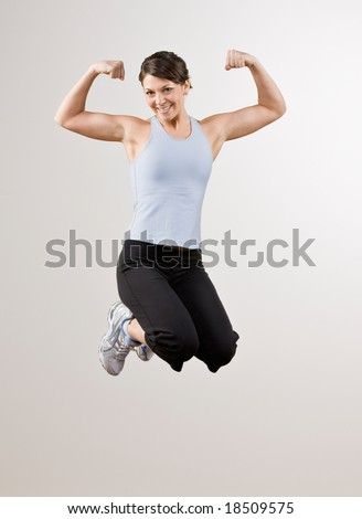 Strong, athletic woman flexing biceps while jumping in mid-air - stock photo