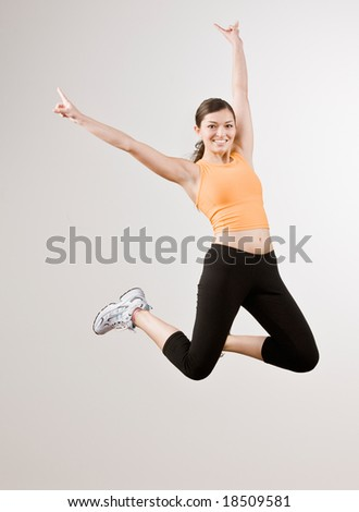 Strong athletic woman in sportswear excitedly jumping in mid-air - stock photo