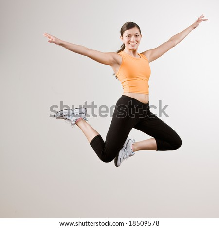 Strong athletic woman in sportswear jumping in mid-air - stock photo