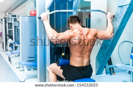 strong athletically built sportsman doing back exercises in a gym - stock photo