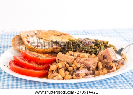 Strong back Light on Soul Food Supper of Chunks of Spam in Black-eyed Peas with Collard Greens and sliced tomatoes.  Seasoned with salt pork and chopped red onions.  Blue Gingham  Tablecloth. - stock photo