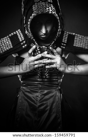 Strong, Beautiful brunette woman in armor formed by mirrors - stock photo