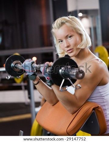 Strong beautiful woman lifting heavy weights - stock photo