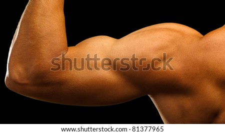 strong biceps on a black background - stock photo