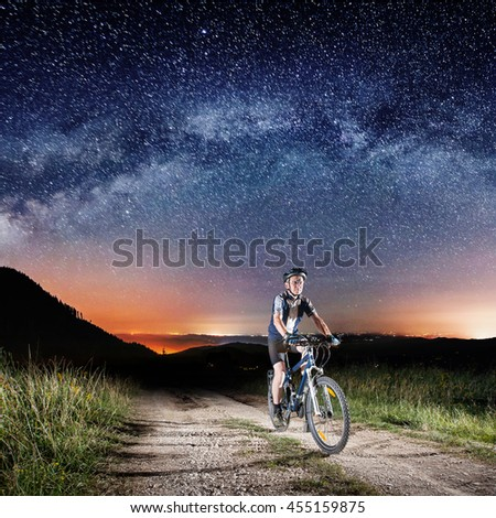 Strong biker biking his bicycle in the night under Starry Sky on the mountain road. Square picture - stock photo