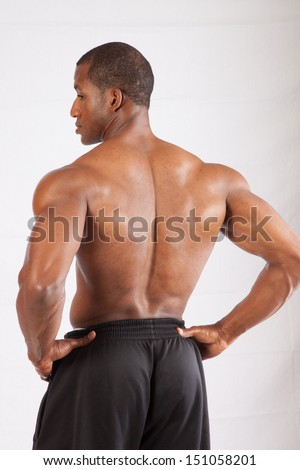 Strong black man topless, with muscles bare, with his back to the camera