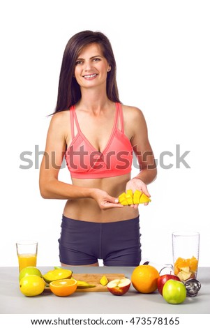 Strong bodybuilder fitness girl with a nice sculpted body making a smoothie from fruits with a blender on white background.