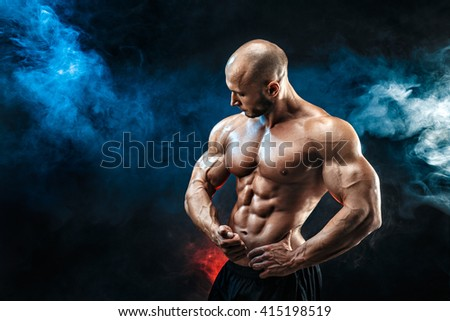 Strong bodybuilder man with perfect abs, shoulders,biceps, triceps, chest. - stock photo