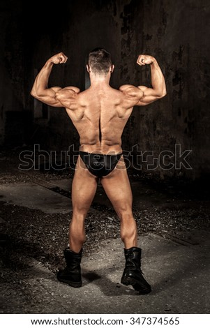 Strong bodybuilder posing in abandoned place