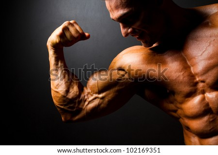 strong bodybuilder posing on black background - stock photo