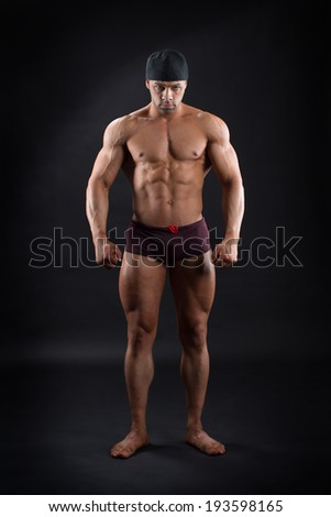 Strong bodybuilder standing against isolated background and showing his powerful muscles