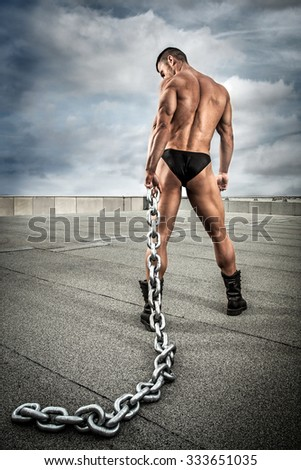 Strong bodybuilder with chain on the roof