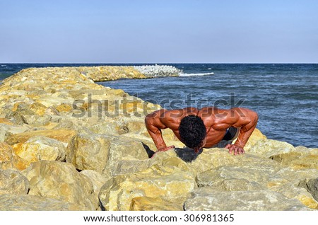 Strong bodybuilder with six pack.Fitness trainer with perfect abs, shoulders,biceps, triceps,chest, flexing his muscles on the beach, training in vacation, doing push ups in the sand - stock photo