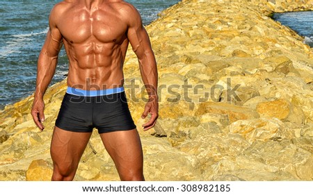 Strong bodybuilder with six pack.Fitness trainer with perfect abs, shoulders,biceps, triceps,chest, flexing his muscles on the beach with sea waves on the background, training in vacation - stock photo