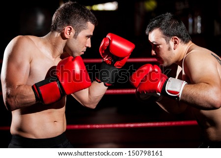 Strong boxer and his opponent during a box fight in a ring - stock photo