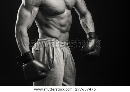Strong boxer on a black background. Brawny guy in boxing gloves.