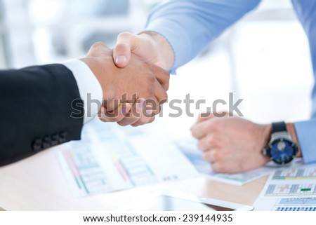Strong business handshake. Close-up view of a handshake while two successful businessman shaking hands at the table against each in the business office in formal wear and work at a laptop. - stock photo