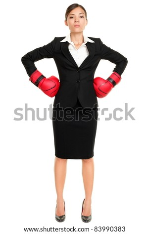 Strong business woman boss executive concept. Businesswoman standing intimidating wearing boxing gloves ready for the competition. Confident attitude by young mixed race female model in suit. - stock photo