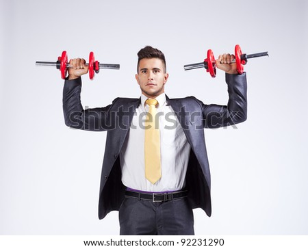 Strong businessman lifting heavy weights - stock photo