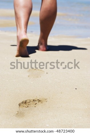 Strong calves on someone walking on the beach and leaving their footprints - stock photo