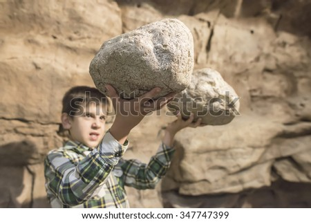 Strong child holds heavy stones.  - stock photo
