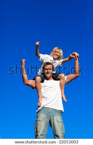 Strong child sitting on his father's shoulders against blue sky - stock photo