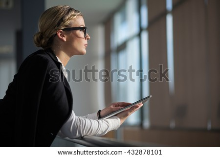 Strong, confident, business woman standing in an office building hallway, holding tablet computer - stock photo