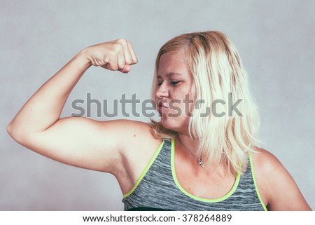 Strong confident muscular woman flexing her muscles. Young blond sporty female showing arm and biceps. - stock photo
