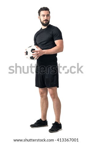 Strong confident soccer player holding ball with both hands looking away. Full body length portrait isolated over white background.  - stock photo