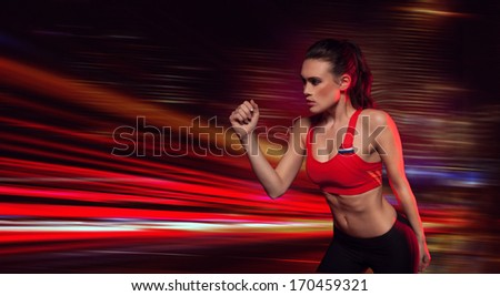 Strong determined female athlete in sportswear with her arm raised as though jogging while working out during training in a health and fitness concept with copyspace - stock photo