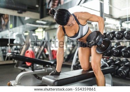 Strong female exercising with barbell in gym