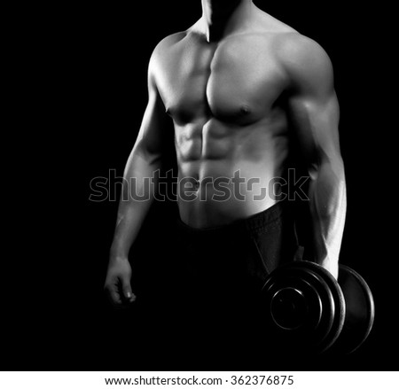 Strong, fit and sporty bodybuilder man with a dumbbell in grayscale. - stock photo