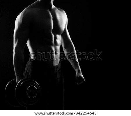 Strong, fit and sporty bodybuilder man with a dumbbell in monochromatic. - stock photo