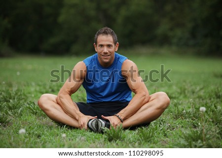 Strong fitness man stretching before his workout - stock photo