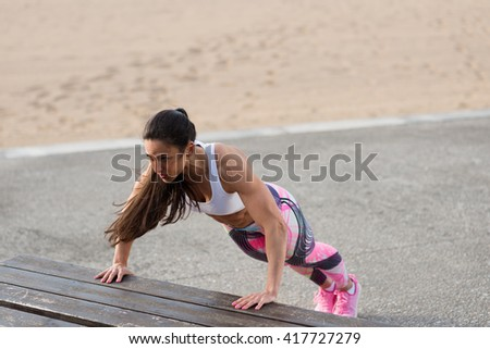 Strong fitness woman doing push ups for chest and arms strength workout. Female muscular motivated athlete training outside. - stock photo